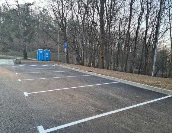 Nuotraukoje suremontuota mašinų stovėjimo aikštelė. Naujame asfalte išbraižytos baltos linijos, kurios žymi mašinų stovėjimo vietas.