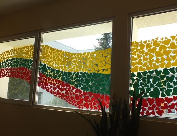 Matyti trys mokyklos laiptinės langai. Visi šie langai papuošti lietuviška trispalve, kuri yra sudėliota iš vaikų iškarpytų geltonų, žalių ir raudonų širdelių. Tarp širdelių yra tarpai, kad širdelės neužengtų pro langą sklindančios šviesos. Ši vėliava pavaizduota kaip širdelių bangą, kylanti nuo pirmojo lango apačios, einanti per vidurinio lango vidurį link trečiojo lango viršutinės dalies.