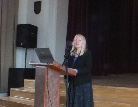 Ketvirtoje nuotraukoje užfiksuota Vilniaus pilių valstybinio kultūrinio rezervato vyriausioji specialistė Angelė Čepėnaitė, pristatanti projektą, skirtą jaunimui. Ji stovi už kalbėtojo tribūnos, ant kurios matyti atvertas nešiojamas kompiuteris. Kalbėtojos palaidinė violetinė, ji pasipuošusi karoliais aplink kaklą, jos švarkas juodas, sijonas išmargintas tamsiais raštais mėlyname fone. Jos plaukai šviesūs, nuotaika pakili.