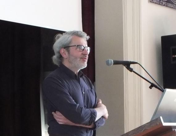 Nuotraukoje užfiksuotas žinomas mūsų šalies fotomenininkas Arūnas Baltėnas, pasakojantis vaikams kaip fotografuoti kraštovaizdį. Jis stovi prie pranešėjų tribūnos ir pasakoja žodžiu, nenaudodamas kompiuterio. Fotomenininkas yra apsirengęs juodais marškiniais, atraitotomis rankovėmis, jis laiko rankas sukryžiavęs ant krūtinės, nešioja akinius. Jo šukuosena su sklastymu ant šono, plaukai pražilę.