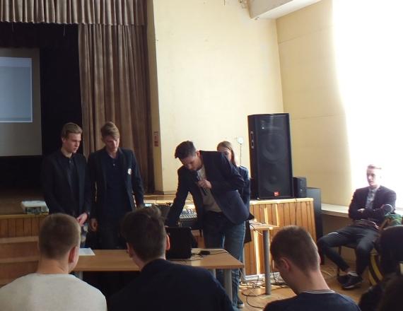Šeštoje nuotraukoje užfiksuotas mokinių referatų pristatymo vaizdas. Trys jaunuoliai stovi prie stalelio veidu į žiūrovus. Jie tvarkingai susišukavę, du iš jų apsirengę juodais marškiniais ir juodais švarkais. Trečiasis kairėje rankoje laiko mikrofoną, o dešine ieško kompiuterio monitoriuje savo pristatymo, kad galėtų jį pademonstruoti susirinkusiems mokiniams ir mokytojams. Jis apsirengęs šviesiais sportiniais marškinėliais ir juodu švarku. Jo du bičiuliai ketina prisidėti pasakodami, nes tai jų bendras kūrinys. Už šio stalelio matyti kitas stalelis, prie kurio veidu į klausytojus sėdi mokinė, vedanti renginį. Kitas vedantysis yra įsitaisęs netoliese ant kėdės prie lango. Nuotraukoje matyti iš nugaros pirmoje eilėje sėdintys jaunuoliai. Du iš jų apsirengę sportiniais marškinėliais, vienas juodu švarku. Visi tvarkingai trumpai apsikirpę.